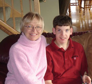 Blonde short haired woman in her 40s with a pink shirt seated on a couch beside a young teenage boy, brown hair red polo shirt in a livingroom