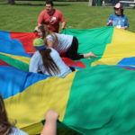 Two individuals crawling on top of colourful parachute. Third individual can be seen in the background waving the parachute as part of a group game.