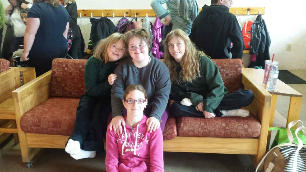 Three young girls seated together on a couch, one young girl seated on the floor in front pose for a group photo