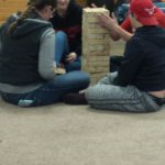 4 School aged individuals build a wooden tower on the ground for a game of Jenga