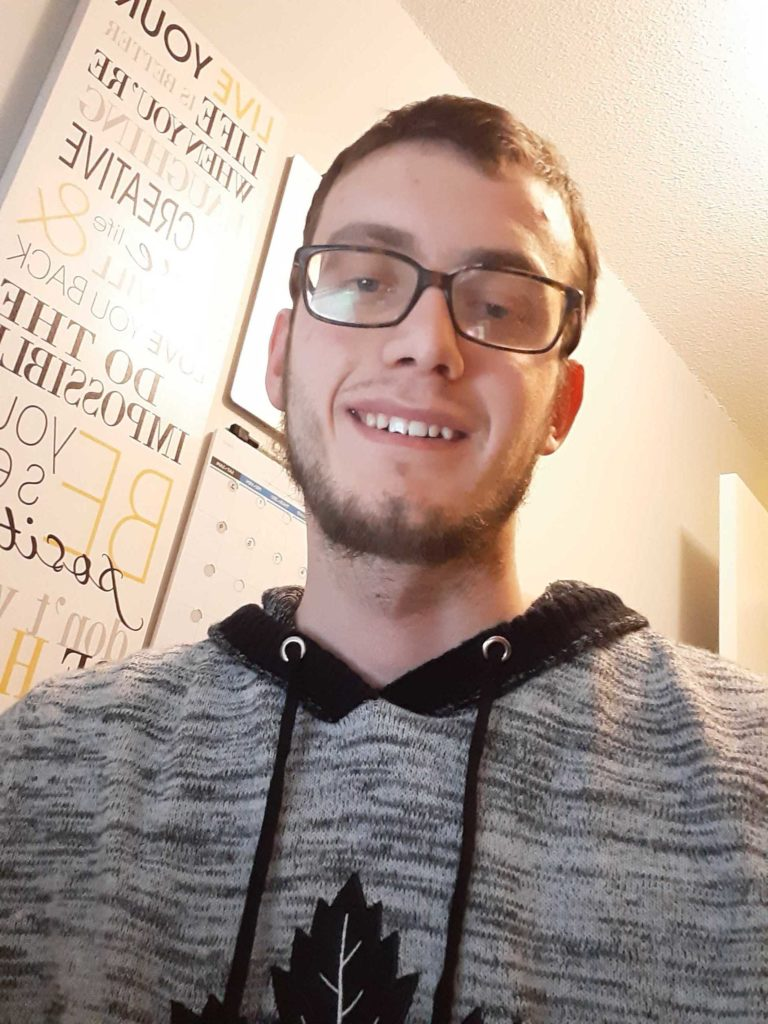 Young male with glasses and brown hair poses for a selfie
