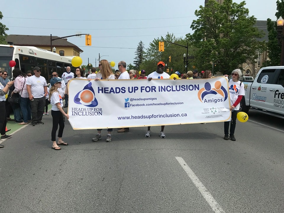 Individuals gathering at the first annual Abilities & Inclusion Movement Event. Heads Up for Inclusion banner leads the parade.