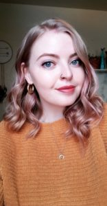 Young woman with blonde hair with pink tones smiles for a self portrait