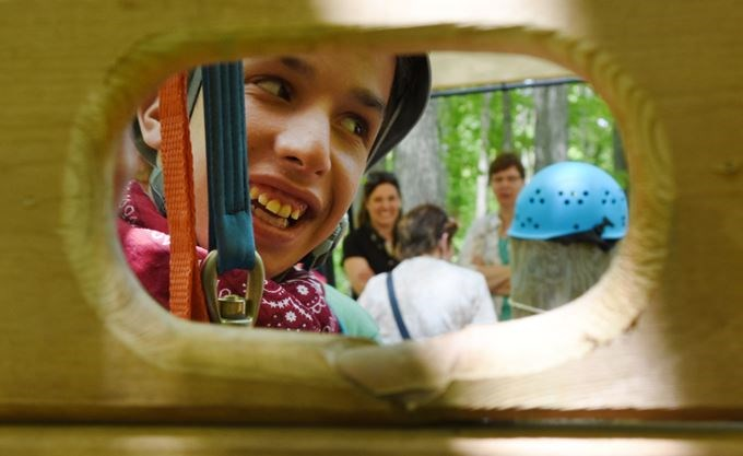 Through a wooden rectangle there is a young individual connected to a harness. The individual is smiling happily