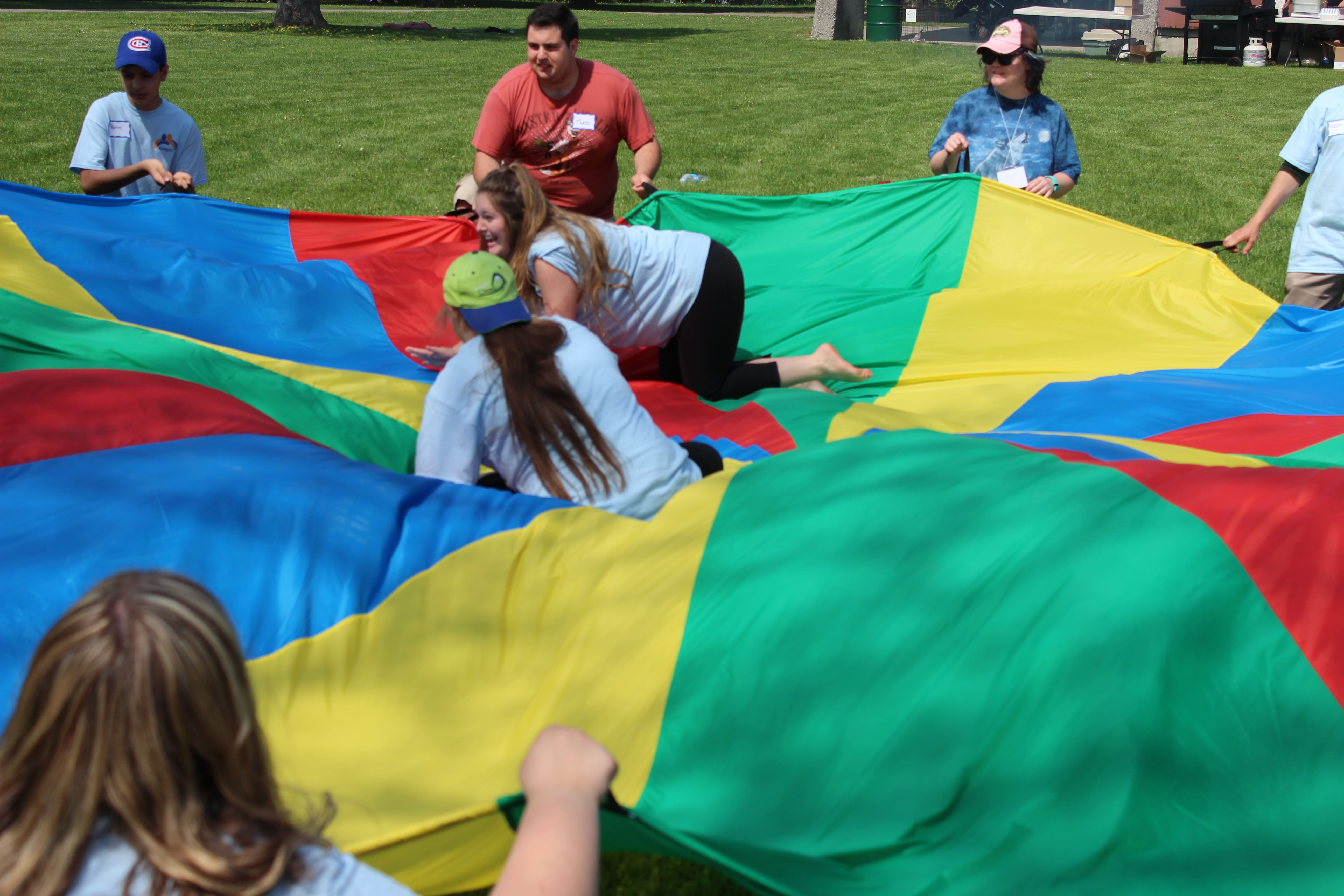 School-aged individuals play with a large parachute