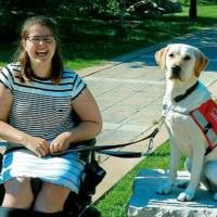 Young woman seated smiles for a photo with her service dog