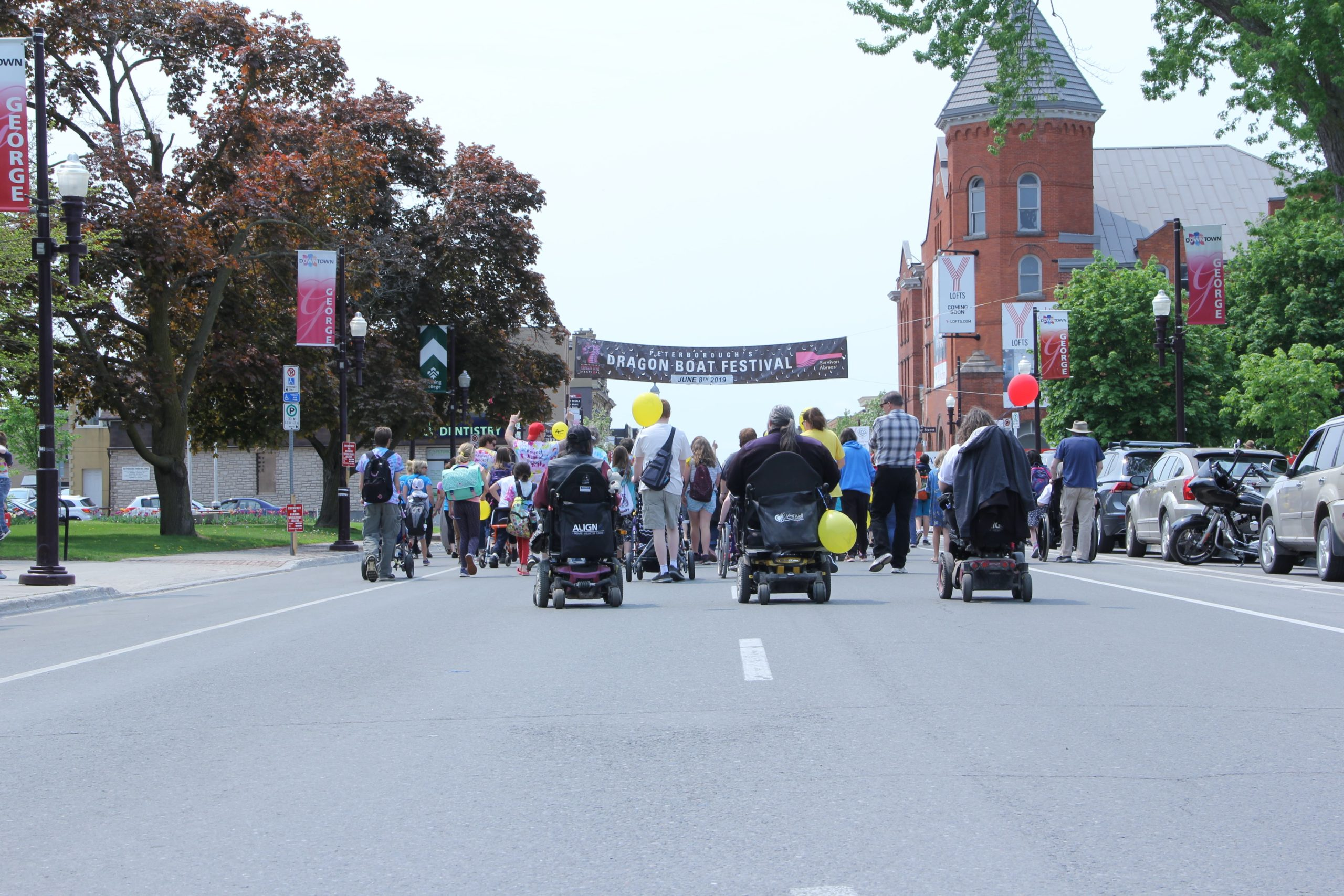 Various individuals walking and moving down George Street in Peterborough for the first Annual Abilities and Inclusion Movement