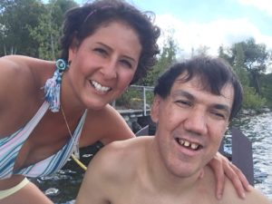 Older woman poses for a picture with a younger male at a cottage lake. Both individuals smile brightly