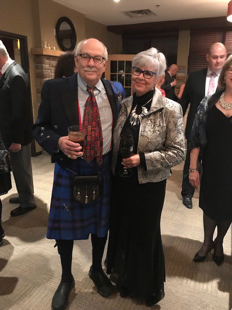 Older gentleman poses in blue tartan kilt with older woman for a photo.