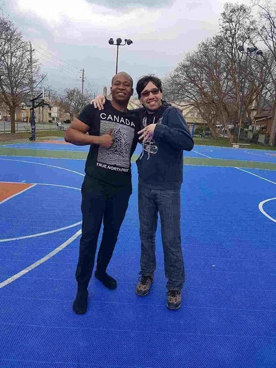 Two young men with arms wrapped around each other are standing and smiling at the camera. They are standing on a bright blue basket ball court. Trees and residential buildings are seen in the background.