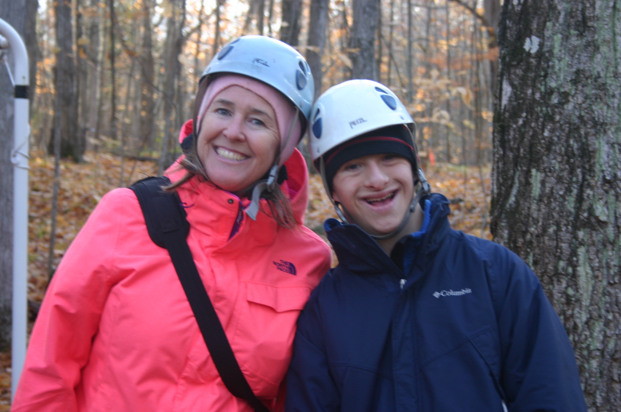 A woman and a younger man are standing together outside in Autumn. They are both wearing helmets and have their heads resting on eachothers and smiling at the camera.