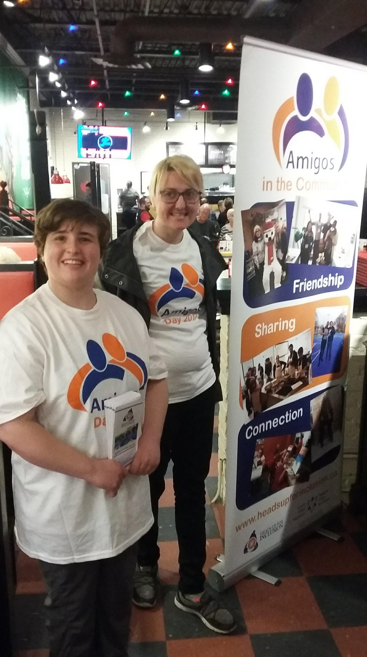 Two women in Amigos T-shirts standing beside a banner.