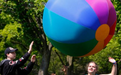 Three school-aged individuals play with a large omnikin ball