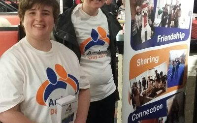 Two young adults stand side by side in amigos t-shirts smiling at a celebrity serving event