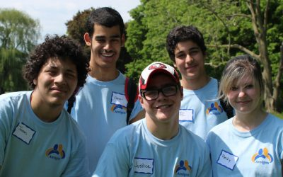 A group of 5 students are huddled together in a group. They are all wearing blue Amigos t-shirts and are standing outside in the sun. Pictured behind them is a local park with grass and trees.