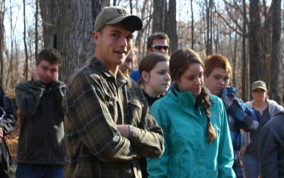 Group of students standing in a forest learning from an offscreen instructor