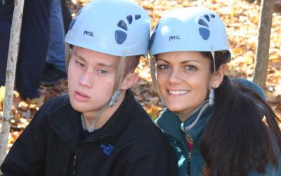 A young boy poses for a picture with an adult woman also wearing a helmet